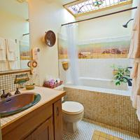 Adobe Rose Inn Our Sam Hughes room features a deep, soaking tub with artistic mural tile